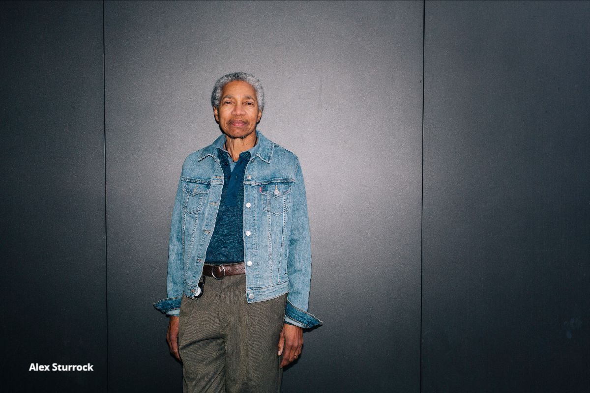 Musician Beverly Glenn-Copeland, an older black man with a short grey afro, wearing a light blue denim jacked, a dark blue button up, a brown belt, and green pants, leans against a grey wall as he calmly looks into the camera.