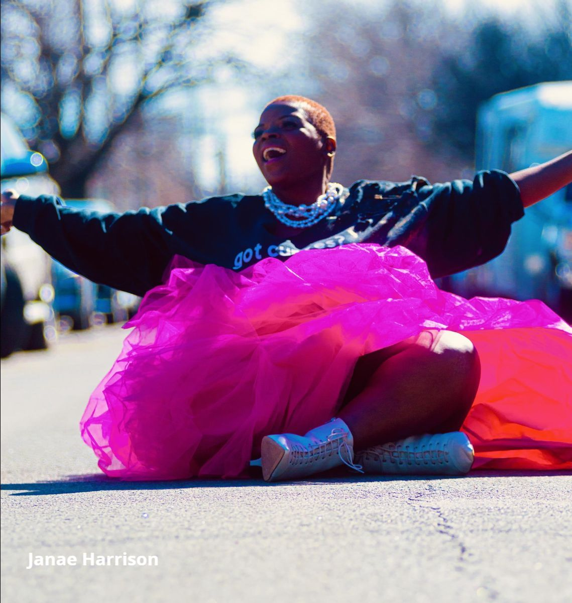 """Donna Perry, a Black woman, sits crosslegged with her arms outstretched on a paved road. She is smiling and looking off to the left, and has close cropped reddish brown hair, multiple strands of pearls around her neck, and is wearing a black sweater that reads """"got curves?"""" in white, a magenta tulle skirt, and iridescent heeled boots."""