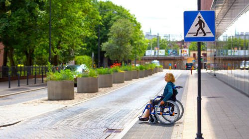 Person in a wheelchair crossing the road.