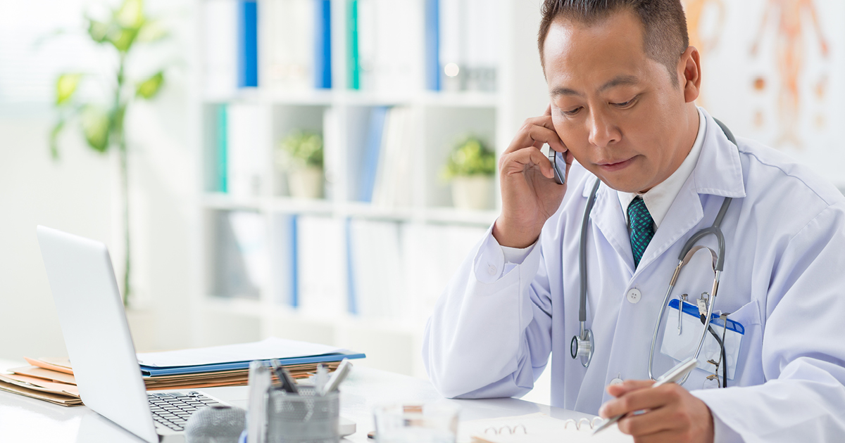 image of a doctor consulting notes while on the phone with a patient