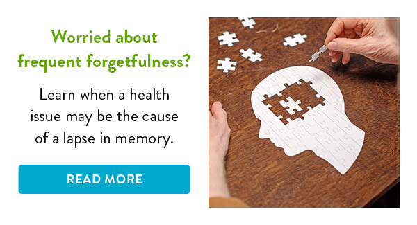 Puzzle pieces on a table in the shape of a human brain.