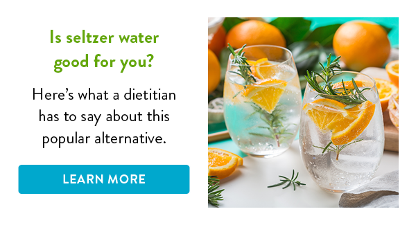 Seltzer water with orange slices and rosemary in a pair of glasses.