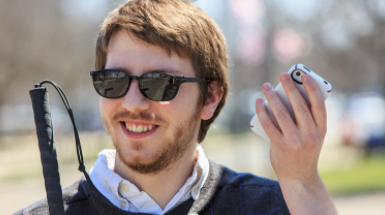 European man with brown hair and sunglasses holding an iphone