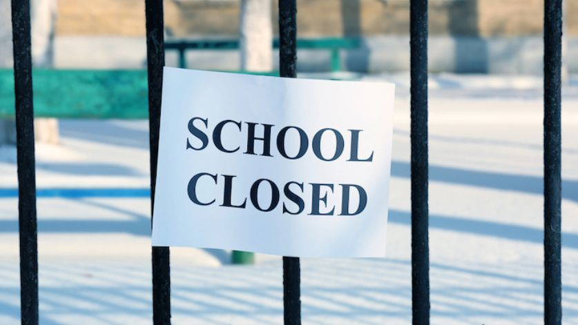 A sign on grill that says school closed