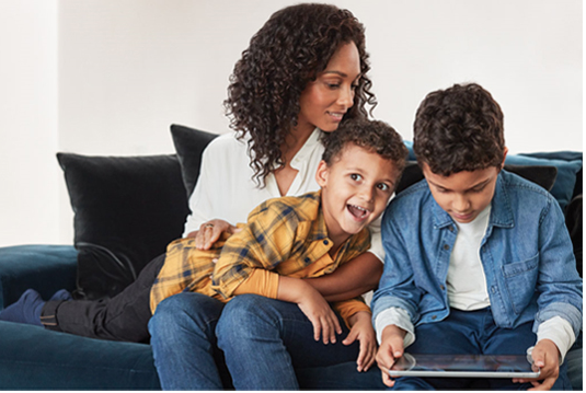Mum with two children on sofa with ipad