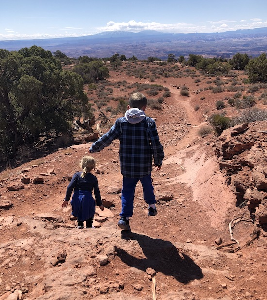 Two kiddos walking on a red dirt trail