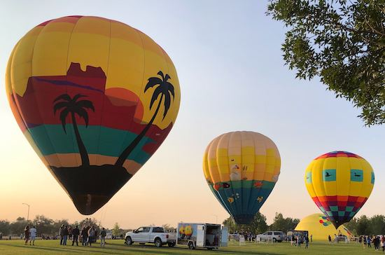 Three hot air balloons lifting off
