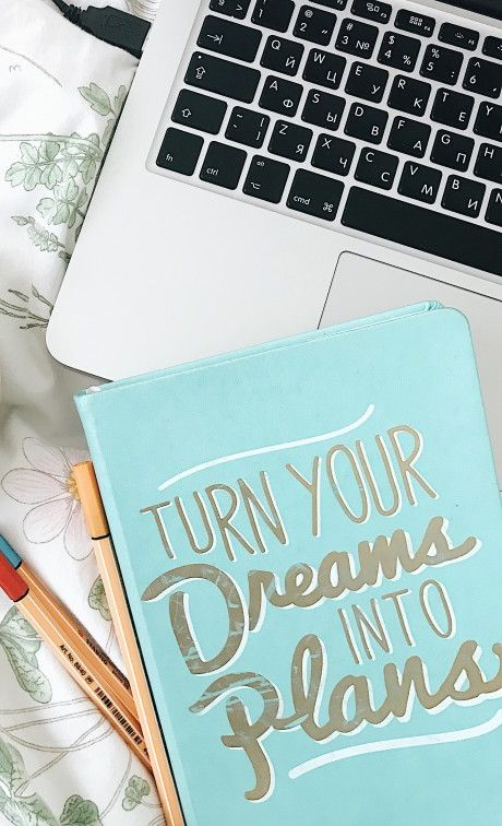 "Laptop and notebook that says ""turn your dreams into plans"""