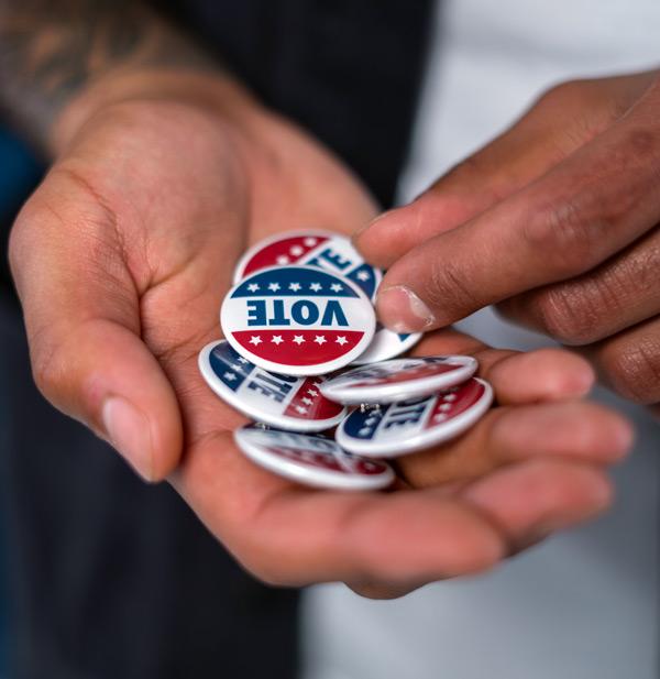 """Man holding """"Vote"""" pins"""