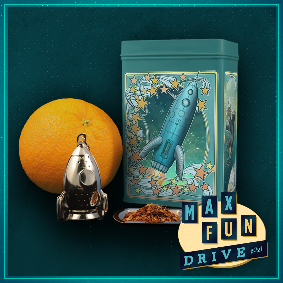An orange next to a teal metal tin with an image of a rocket and stars on the front, with a metal rocket tea strainer and a tray of orange tea in front