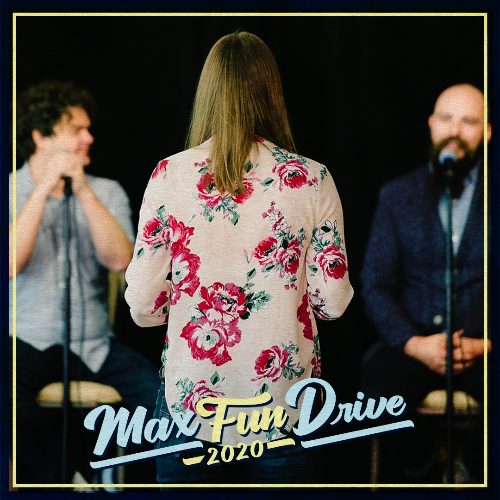 A person in a pink floral shirt standing in front of two MaxFun hosts as if asking them a question during a Q&A