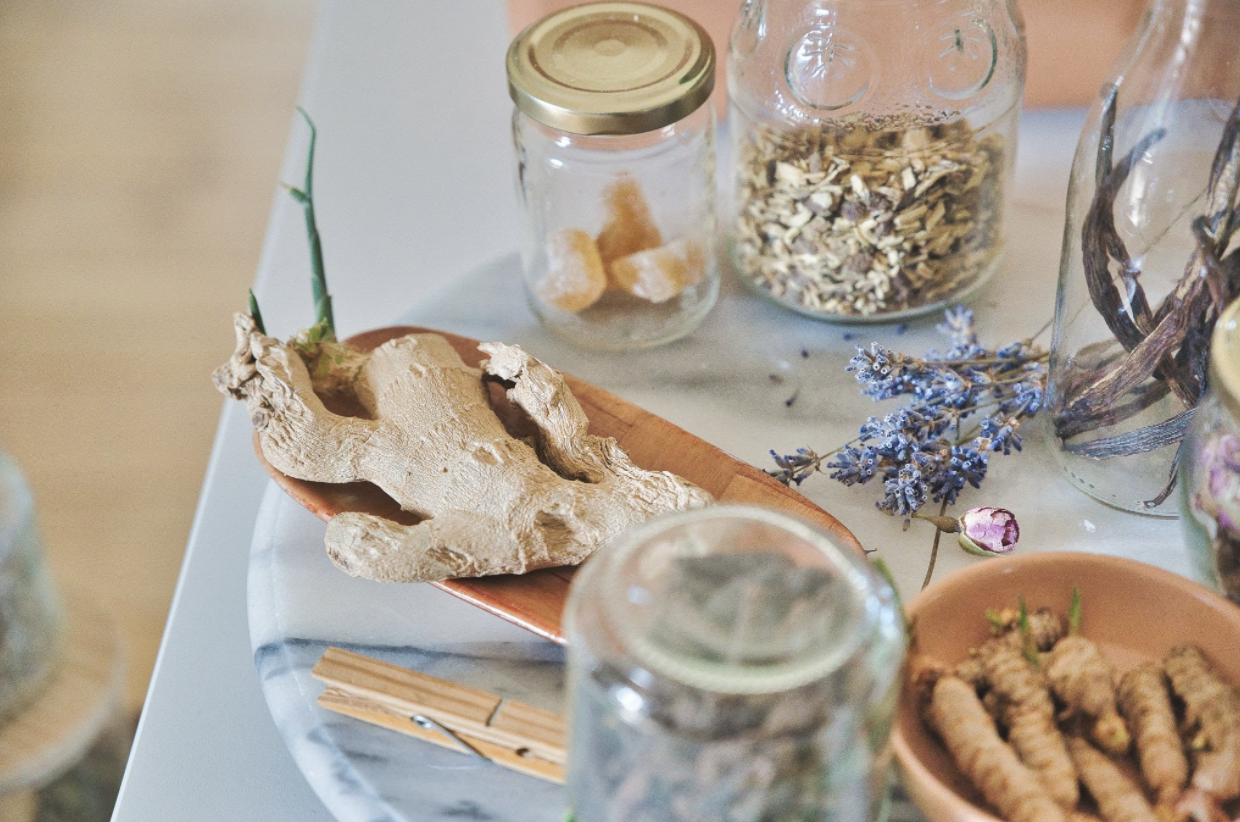 various dried herbs and roots in jars and on trays on a marble table