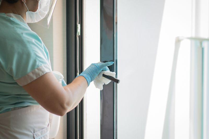 Worker cleaning a door handle