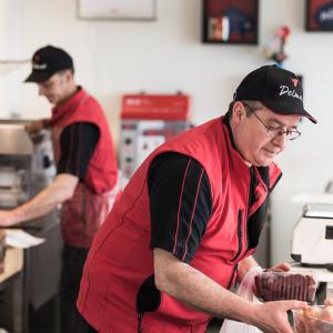 Les risques de TMS du Maître Artisan Boucher de la Boucherie Delmas portant des barquettes de viande