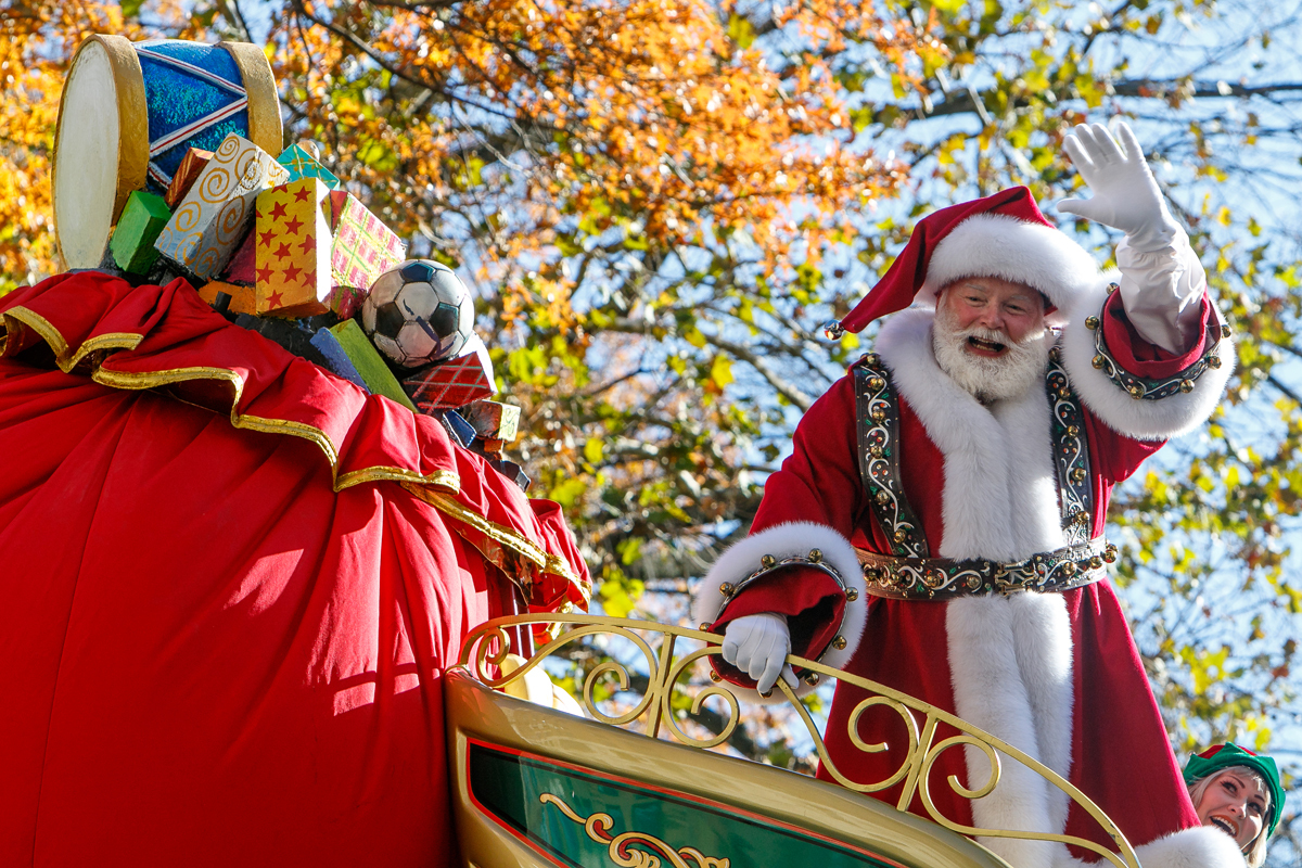 Santa Claus on a sleigh parade float with autumn trees in background.