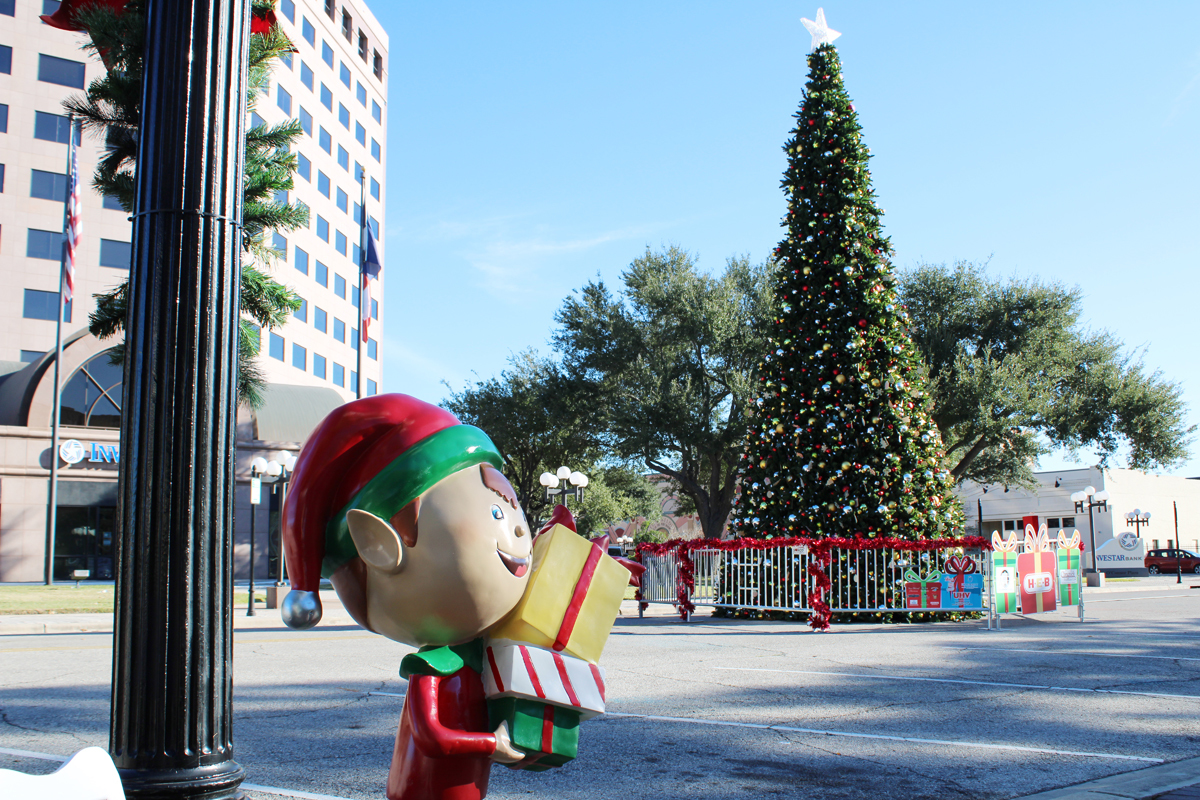 Plexiglass elf sculpture next to lamppost with H-E-B Christmas Tree in the background.