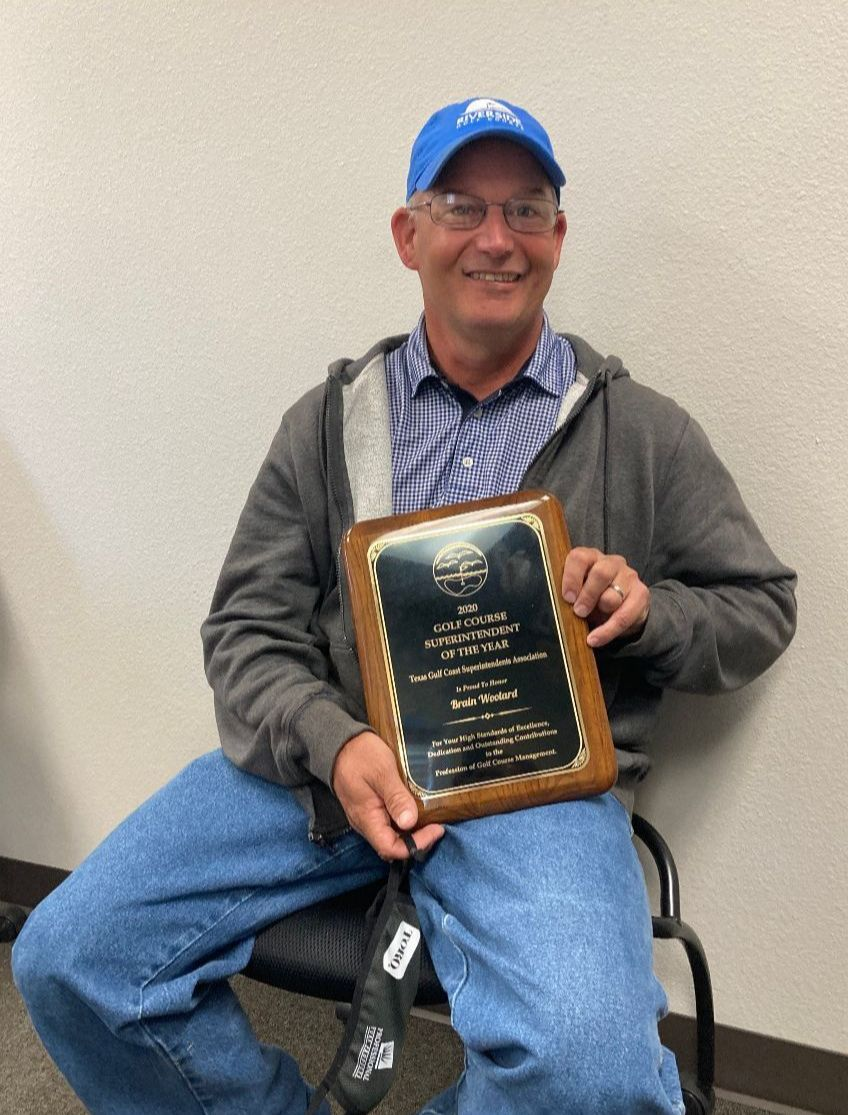 Smiling man, seated, poses with plaque