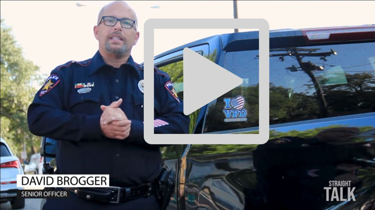 """Senior Officer David Brogger stands in front of car with """"I heart VPD"""" sticker. Play button is displayed."""