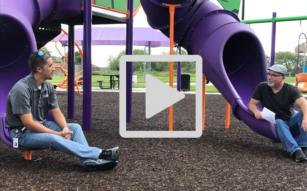 Parks director Jason Alfaro and TOWNtalk host Shane Blucher sit on slides