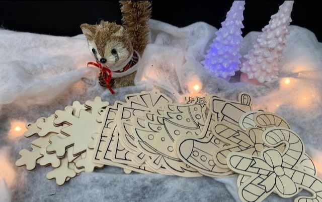 Wooden ornaments with Christmas designs are displayed in a faux snowscape with Christmas lights, mini Christmas trees and a squirrel figurine wearing a red bow