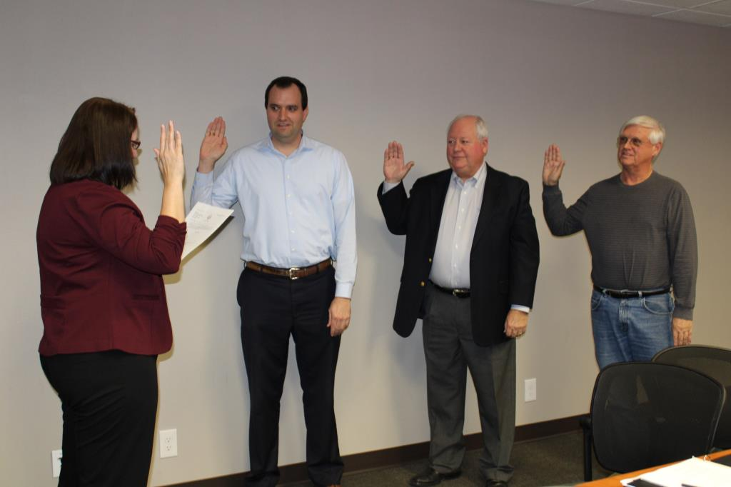 Woman swears in 3 men with hands raised.