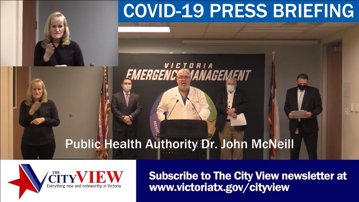 Sign language interpreter, mayor, judge, doctor and health department director at a press conference.
