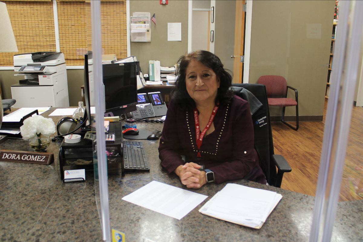 Dora Gomez sits at desk