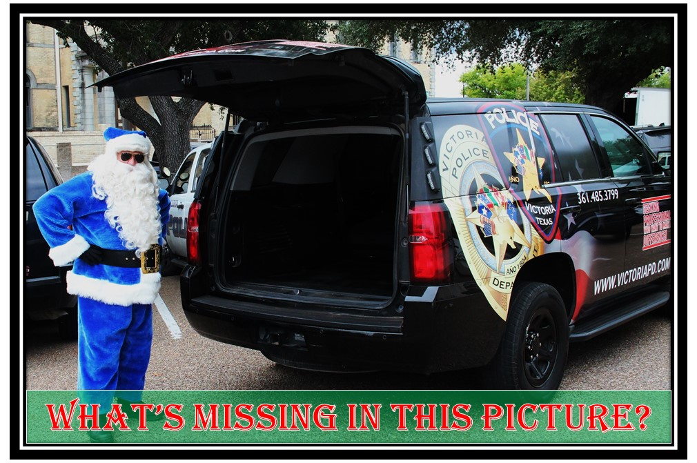 """Santa in blue suit stands next to police cruiser with open hatch showing it's empty. Text reads, """"What's missing in this picture?"""""""