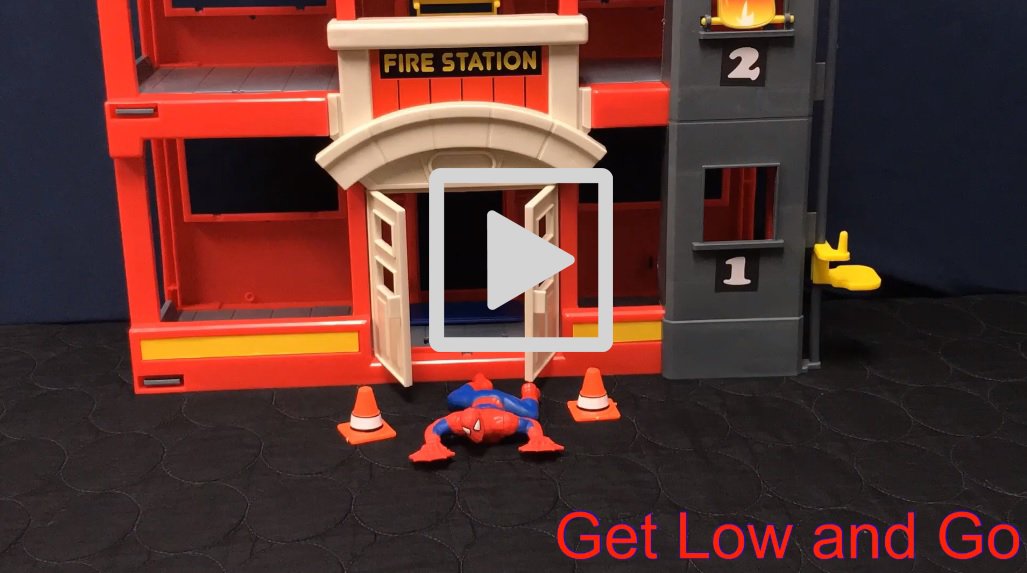 A toy Spiderman figure crawls out of a toy fire station. Play button is displayed.