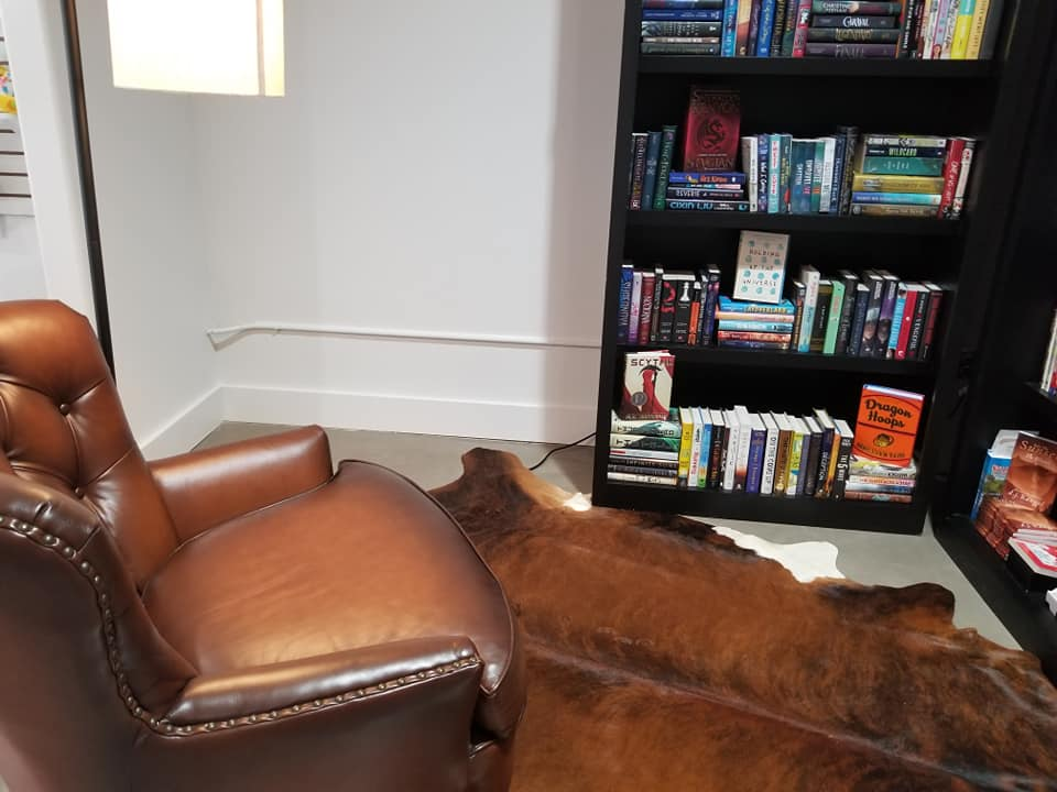 Texian Books interior with bookshelf, reading chair and cowskin rug