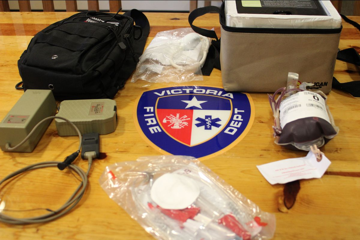 Equipment including an ice chest, a frozen bag of blood and medical tubes displayed on a table.