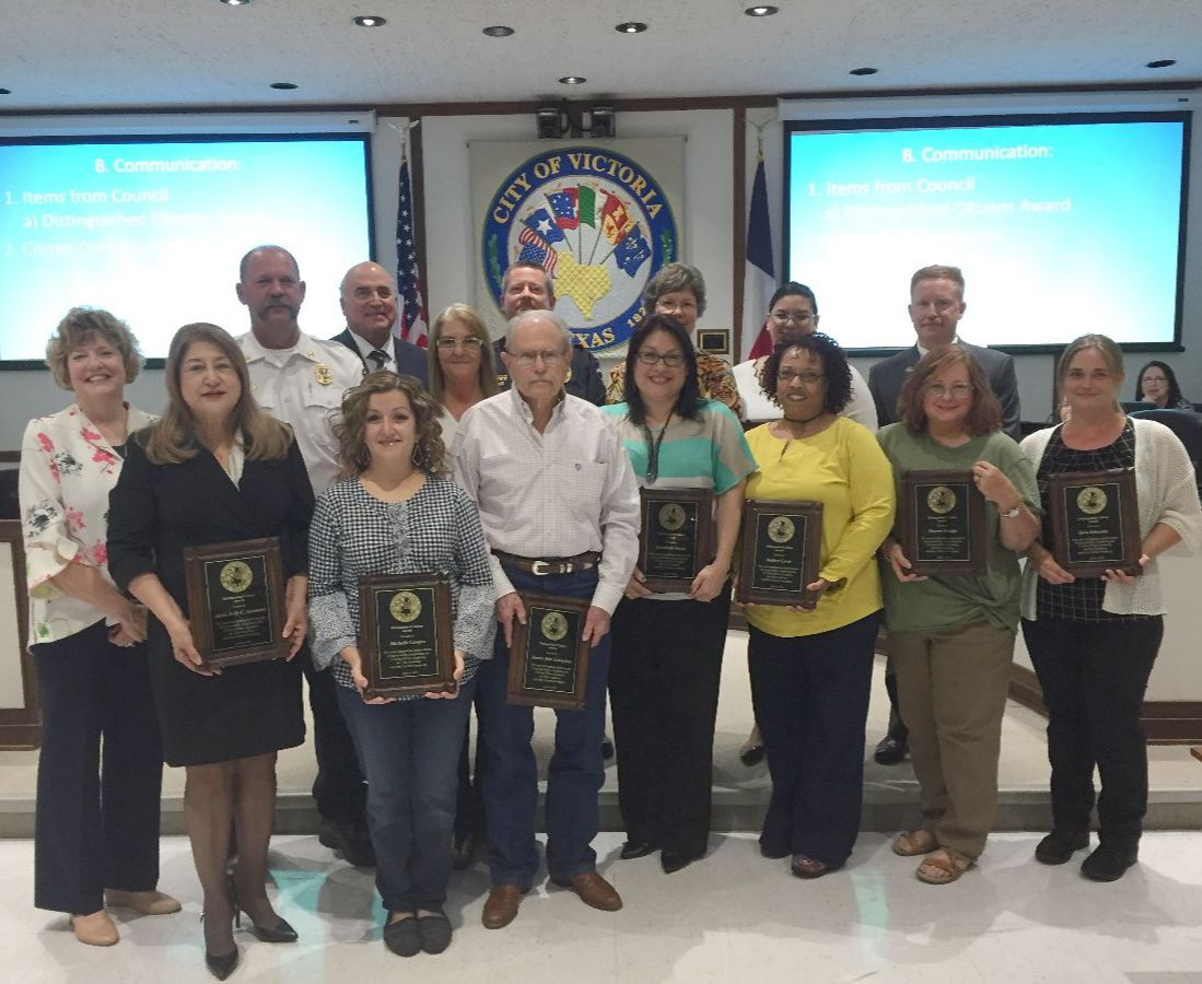 Group of adults pose with plaques in Council chambers surrounded by City officials.