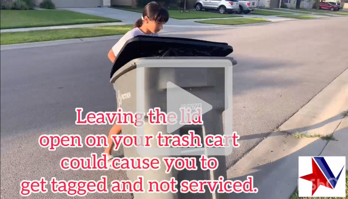 Girl pulls trash cart with lid open