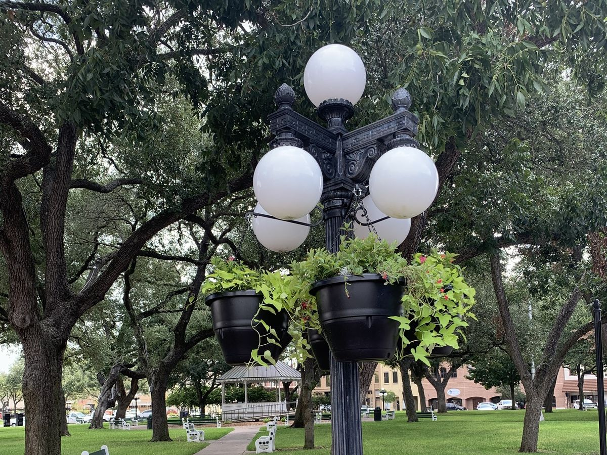 Flower baskets hang from lamppost