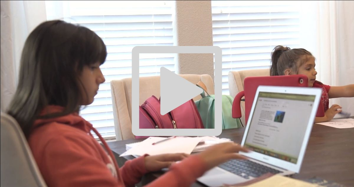 Young girls use laptops at kitchen table