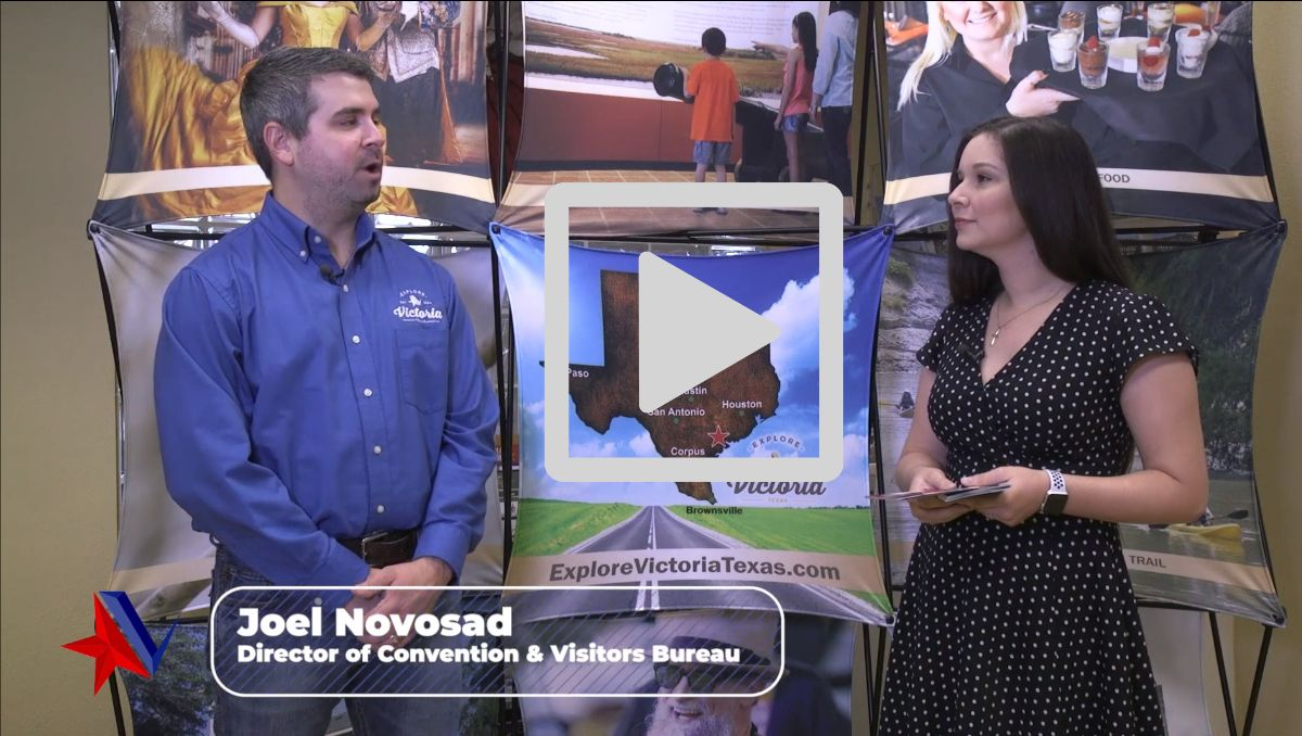 """Joel Novosad speaks with Ashley Strevel in front of Explore Victoria backdrop with tourism photos. Text reads """"Joel Novosad, Director of Convention & Visitors Bureau."""" Play button is displayed."""