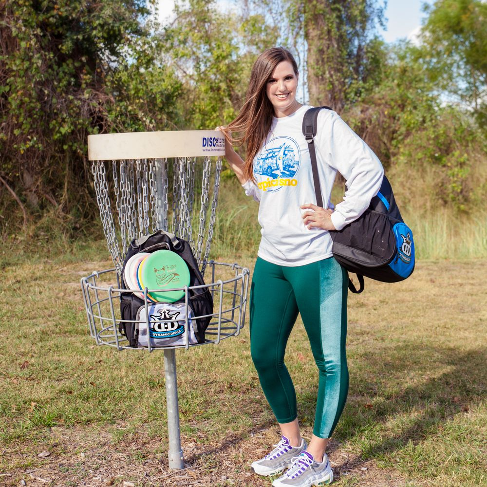 Smiling woman stands near disc golf basket full of discs and a bag.