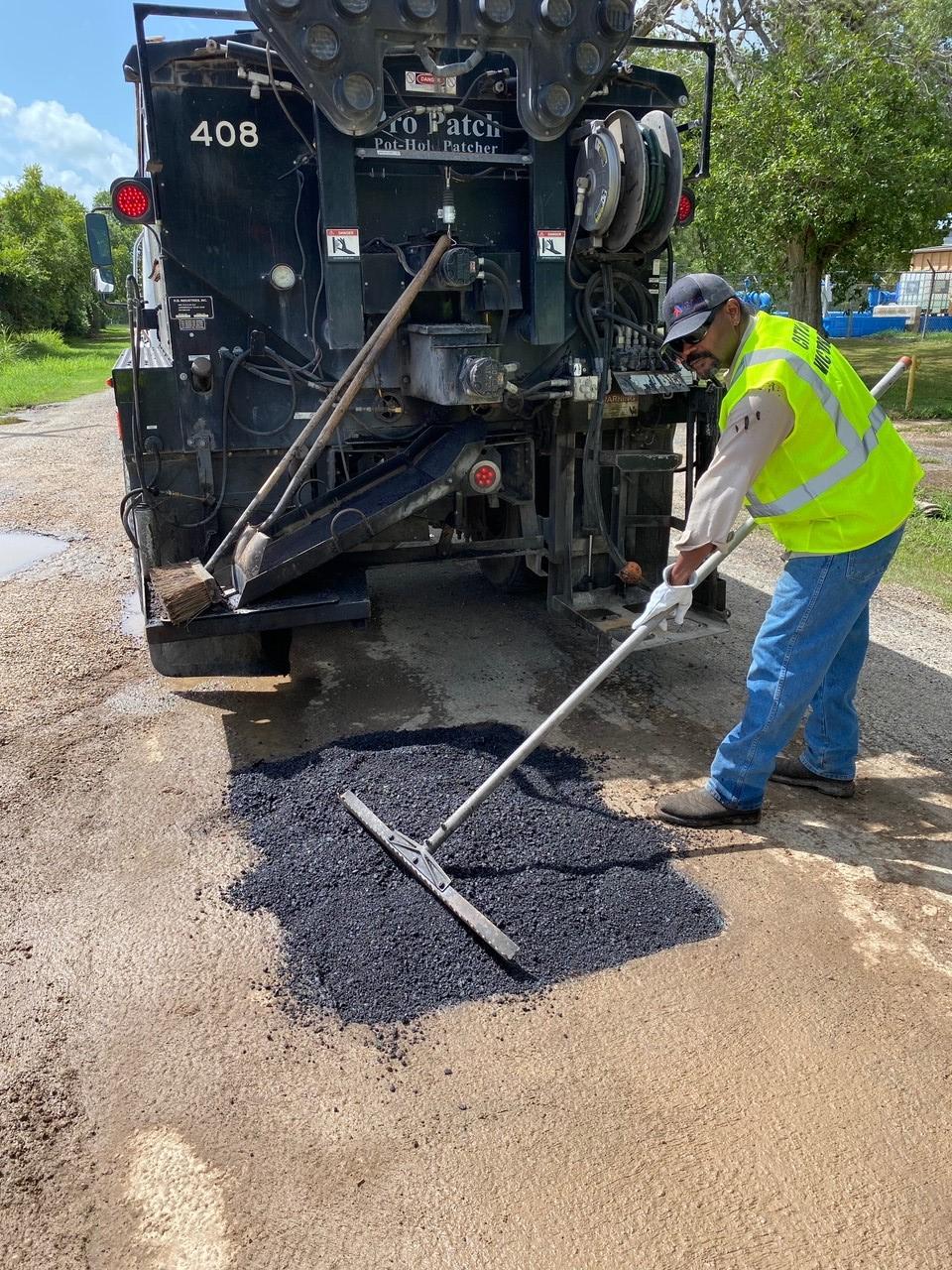 Worker repairs pothole