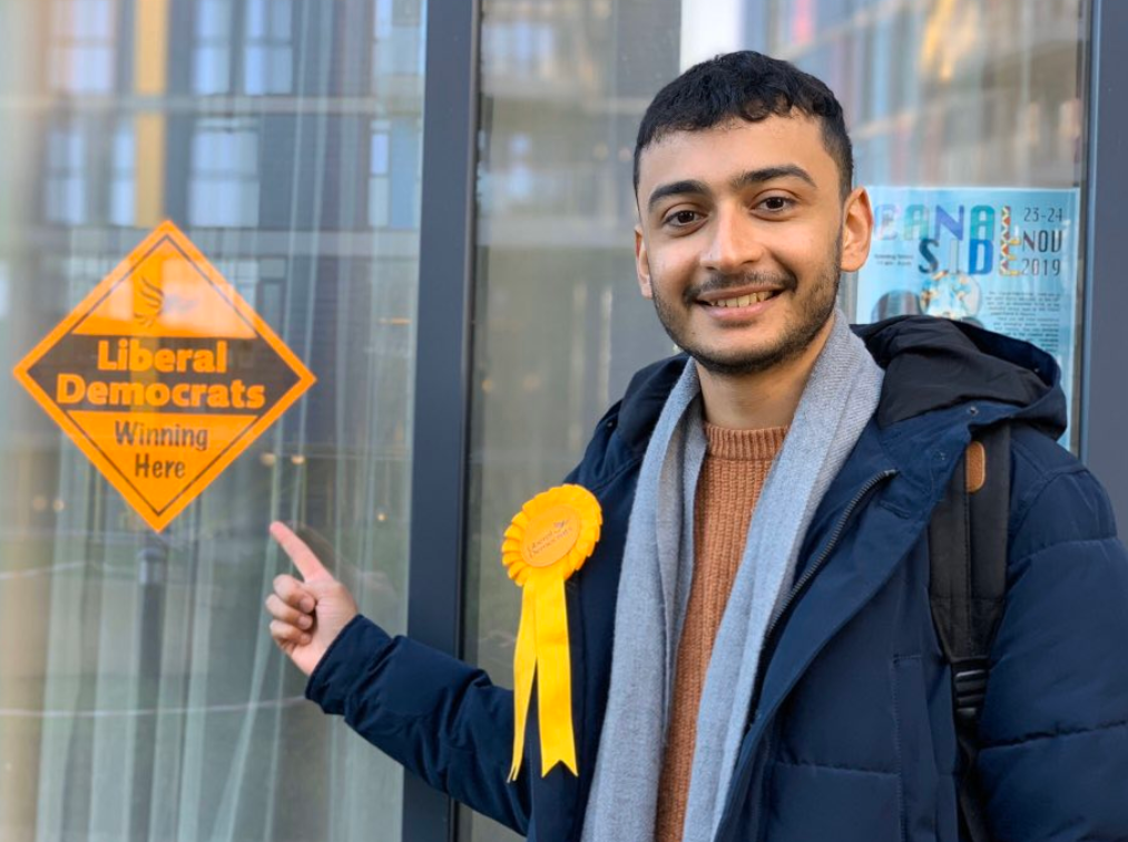 Anton Georgiou pointing at a Lib Dem poster