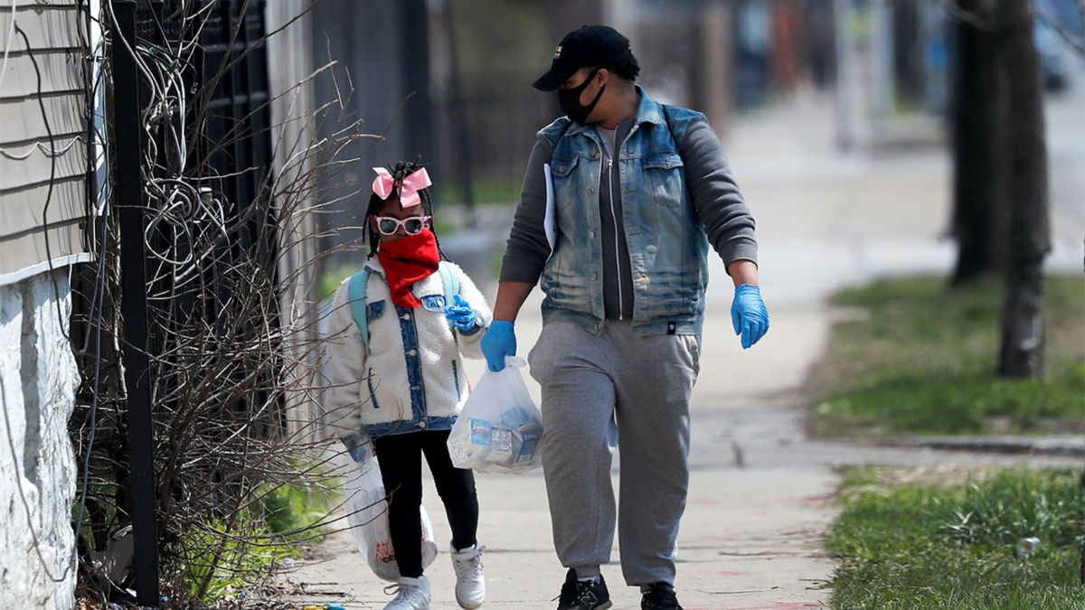 Two black people wearing masks and disposable gloves walking down a sidewalk holding plastic bags filled with either groceries or something else