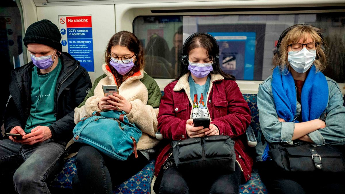 A group of four subway riders sitting next to each other all wear surgical masks, most look down at their phones while one rests.