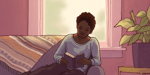 A person with brown skin and brown hair sits on a couch reading a book. There is a window behind them and a plant next to them.