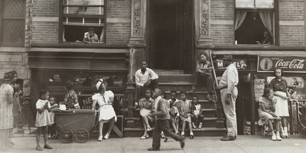 A black and white photo shows people gathered on a stoop and standing on the street nearby