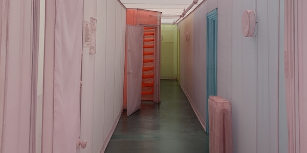 view looking into a replica of the artist's empty apartment in New York made from thin wires and colored mesh in pink, red, blue, and yellow