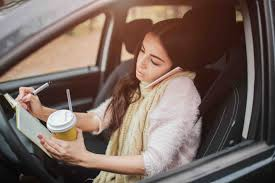 Image of a driver who is distracted by her phone, drinking coffee, & writing notes in a journal.