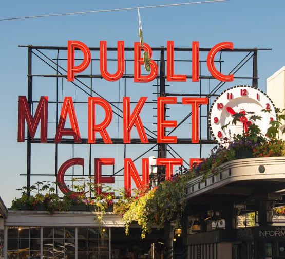 Link takes you to information about Pike Place Market Foundation Covid Update page. Image shows Public Market Center sign at Pike Place Market