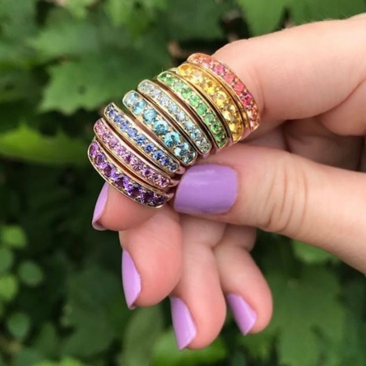 link takes you to see Jane Taylor Jewelry. Image shows stack of rings creating a rainbow on index finger