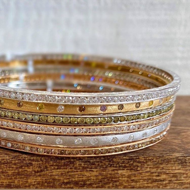 Stack of multicolor diamond bangles in yellow, rose and white gold on a wood table