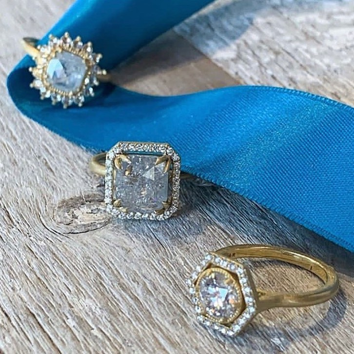 3 rustic diamond rings on a blue ribbon against a light wood background