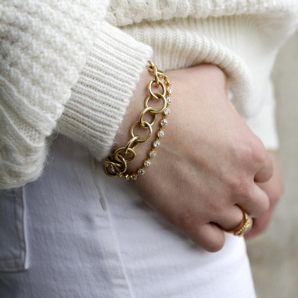 yellow gold bracelets on a wrist with a sweater